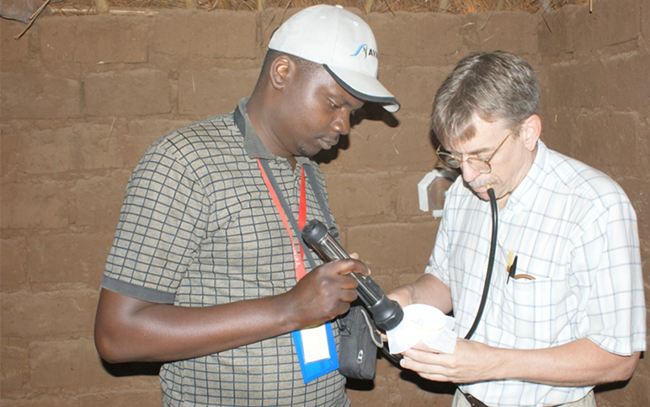 Dr Bangs (right) conducting a wall bioassay to test the efficacy and residual activity of an indoor residual spray used for malaria control.